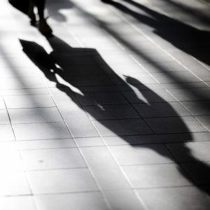 En skugga av en person i Helsingfors centrum i oktober.