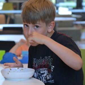 En pojke tittar in i kameran, han äter sin soppa.