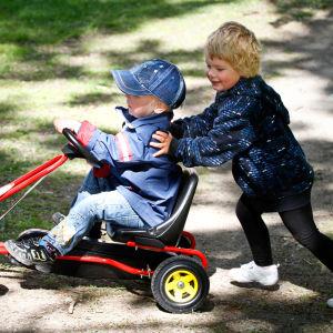 Ett barn sitter på en röd trampbil och ett annat barn skuffar framåt.