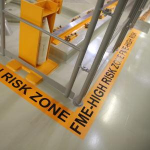 FME High risk zonesta ilmoittava tarra lattiassa Olkiluoto 3 reaktorirakennuksessa.