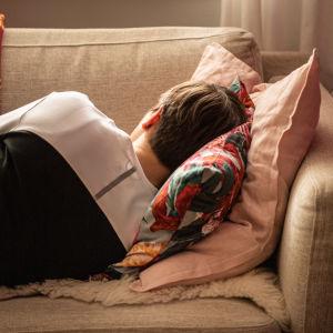 Nainen nukkumassa sohvalla.