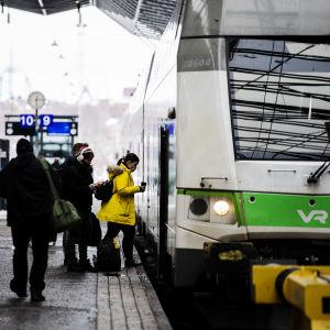 Tågresenärer stiger på ett grönt Intercitytåg på Helsingfors tågstation.