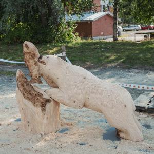 Puuveistos, jossa karhu tavoittelee lohikalaa
