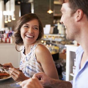 Skrattande par äter lunch på restaurang.