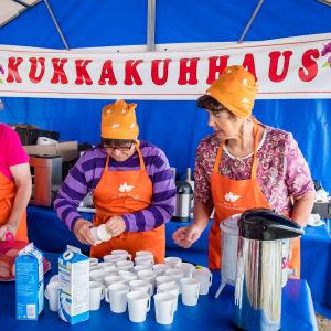 Kukkakuhhauksen kahviteltassa kolme myyjää järjestelee kahvikuppeja ja pullia.