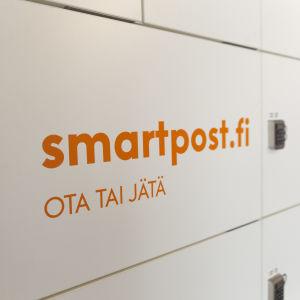 """smartposti.fi -pakettilokero, jossa numerosarjalukko ja teksti """"ota tai jätä""""."""