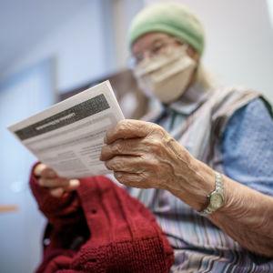Äldre dam håller i sitt vaccinbevis.