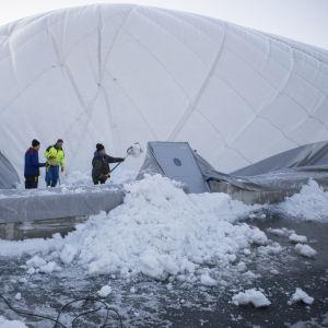 En uppblåsbar idrottshall som rasat iho. Män gräver bort snö som finns ovanpå.