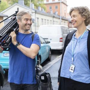 En fotograf i blå t-shirt bär på ett kamerastativ och pratar med en redaktör på gatan.