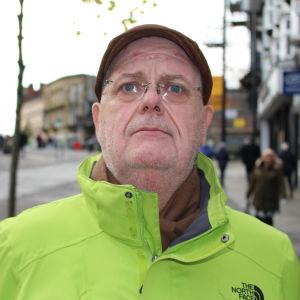 54-åriga Kieran Haunch fotograferad på gågatan i Wigan. Han är iklädd en grann vindjacka och en keps.