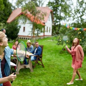 En ung man och en ung kvinna spelar badminton på en gräsmatta framför ett trähus. Några personer sitter vid ett trädgårdsbord och tittar på.