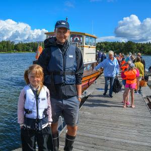En man och en flicka står på en brygga framför en större båt.
