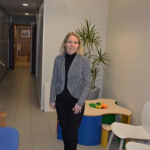 Ljushårig kvinna i korridor.