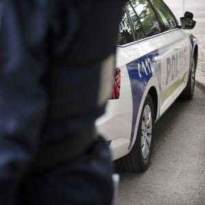 En polis står framför en polisbil.