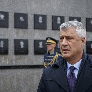 Kosovos president Hashim Thaçi tittar på ett monument.