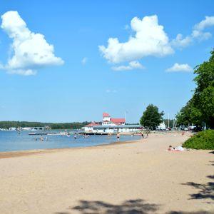 Sandstrand med mycket folk. Många badar i vattnet. En bit strandbyggnad i bakgrunden. En varm sommardag.