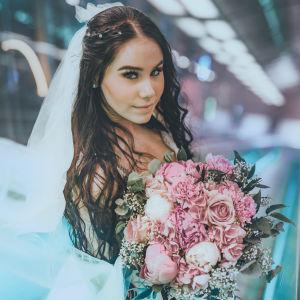 Ronja Mariela hääpuvussa kukkakimppu kädessä