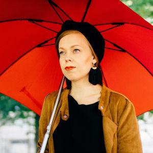 Viitasen Piia -yhtyeen laulaja-lauluntekijä Piia Viitanen lähikuvassa punaisen sateenvarjonalla.