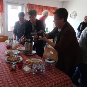 Fyra äldre damer står runt ett bord. En av dem häller upp kaffe i en mugg.