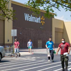 Människor med ansiktsskydd promenerar bort från en Walmart-butik
