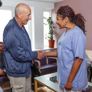 En kvinna tar emot en patient och skakar hand med honom i väntrummet.