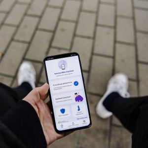 En smarttelefon med coronablinkern på skärmen. E person håller mobilen i handen.