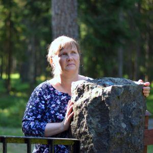 Kvinna vid stenfot intill grind. Ett kors och skog i bakgrunden. Kvinnan har håret uppsatt och bär en blå skjorta med vita blommor på.