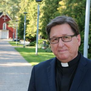Kyrkoherde Martin Fagerudd med Rödsands röda kapell i bakgrunden.