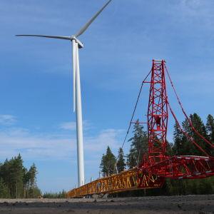 En lyftkran ligger på marken intill ett vindkraftverk.