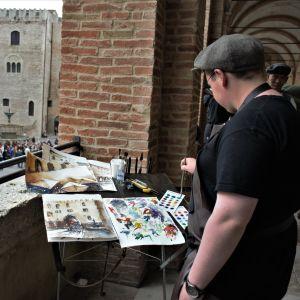 En person står och målar i akvarell med utsikt över ett torg.