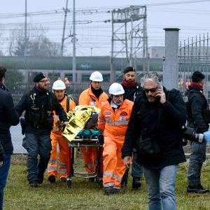 Räddningspersonal evakuerar skadade från olycksplatsen utanför Milano.