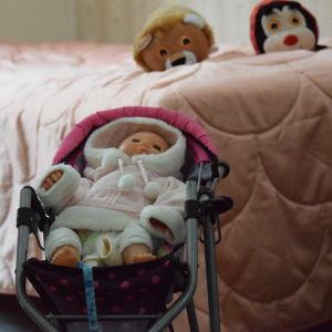 En dockvagn framför en säng var det ligger två kramdjur, ett lejon och en nyckelpiga. Sängöverkastet är rosa.