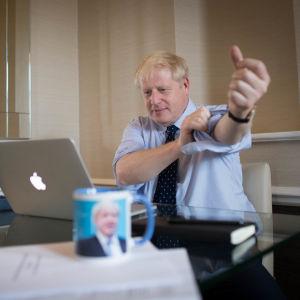 Boris Johnson ses kavla upp ärmarna vid en dator.