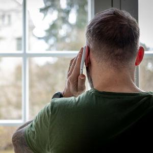 Mies puhuu puhelimessa ikkunan edessä.