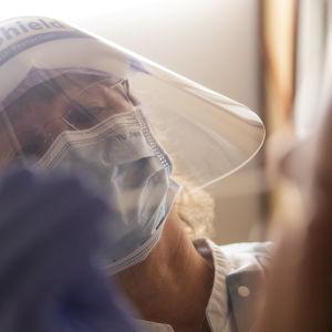 En person iklädd munskydd och visir sträcker ut en handskbeklädd hand mot en annan människas ansikte.