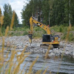 En grävmaskin vid en å.