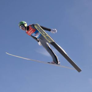 Ilkka Herola flyger genom luften i ett backhopp.