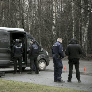 Poliser i mörkblå uniformer står vid en svart paketbil.