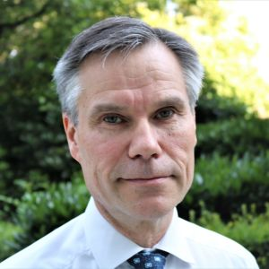 Finlands Natoambassadör Klaus Korhonen fotograferad i närbild. I bakgrunden en lummig trädgård.
