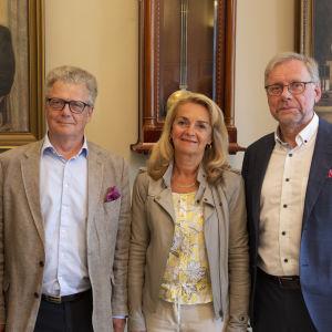 Tre män i kostym och en kvinna står framför porträtt.