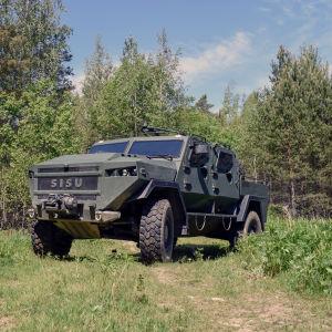Ett militärfordon av modellen SISU GTP 4x4 står i mitten av bilden, runtom gräs och skog.