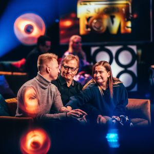 Isä ja aikuiset poika ja tytär istuvat sohvalla kuuntelemassa SuomiLOVE-esitystä.