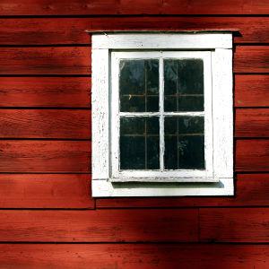 en rödmålad stockvägg med ett vitmålat fyrkantigt fönster med fyra mindre rutor