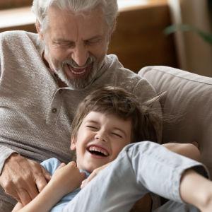 Äldre man och liten pojke sitter i en soffa och skrattar