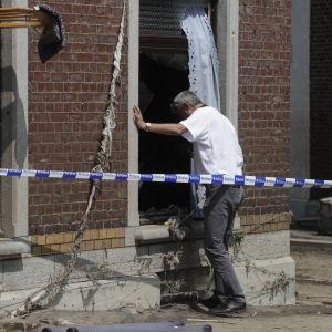 En man kliver in i en byggnad som tagit skada.