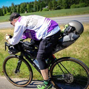 Pyörälijä ajaa lujaa alas mäkeä.