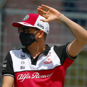 Kimi Räikkönen med Alfa Romeo-tröja, keps och svart munskydd hälsar på publiken.