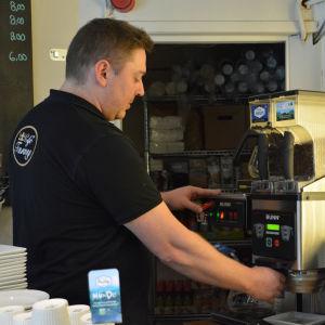 Cafe Fannys företagare står och kokar kaffe.
