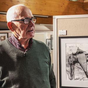 Äldre man i grön ylletröja berättar om svartvita fotografier som föreställer grönländska inuiter.