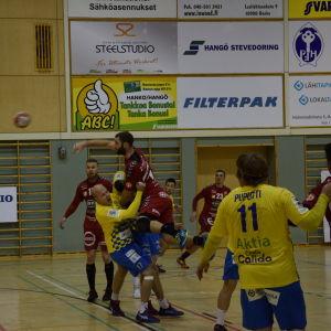 En Cocksspelare hoppar upp för att skjuta bollen medan Fredrik Karlsson i HC HIK försöker stoppa honom.